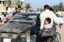 Residents pass by a damaged vehicle a day after a bomb attack in central Baquba