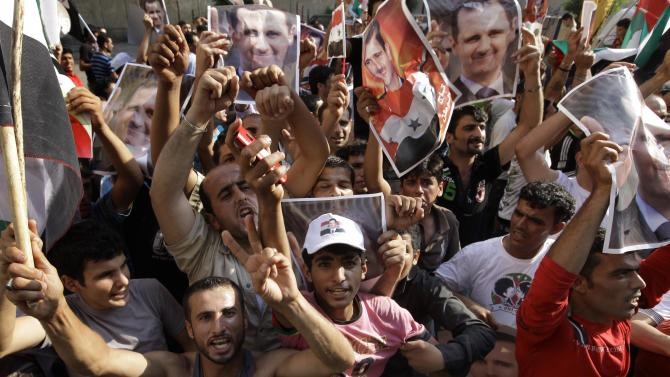 Syrian protesters carry pictures of Syrian President Bashar Assad as they gather outside the Syrian embassy in Beirut, Sunday, July 24, 2011. Nearly 2,000 supporters of Assad gathered outside the Syrian embassy carrying a giant Syrian flag. (AP Photo/Bilal Hussein)