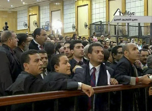 In this video image taken from Egyptian State Television lawyers for the relatives of the slain protesters shout and bicker, apparently over seating, on Monday Aug. 15, 2011 prior to the resumption of the trial of former President Hosni Mubarak.   Mubarak  returned to a Cairo court on a stretcher for the next session of his trial on charges of corruption and complicity in killing protesters during Egypt's uprising. (AP Photo/Egyptian State TV)   EGYPT OUT