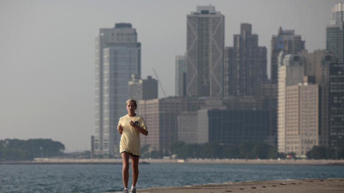 "An early morning jogger passes along the shore of Lake Michigan Wednesday, July 20, 2011 in Chicago. Much of the United States is trapped under a heat ""dome"" caused by a huge area of high pressure that's compressing hot, moist air beneath it, leading to miserable temperatures in the mid-90s to low 100s and heat-index levels well above 100 degrees. (AP Photo/Kiichiro Sato)"