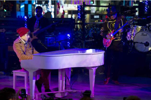 Justin Bieber,left, and Carlos Santana perform in Times Square during the New Year's Eve celebration, Saturday, Dec. 31, 2011, in New York. (AP Photo/Charles Sykes)