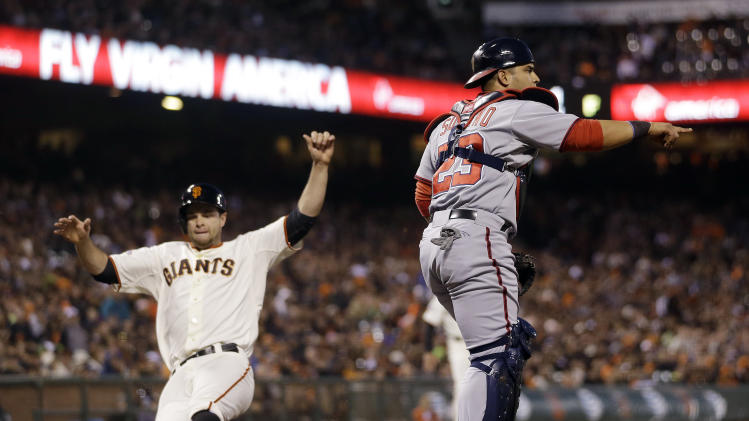 San Francisco Giants' Brandon Belt, left, scores after a sacrifice bunt from Ryan Vogelsong next to Washington Nationals catcher Jhonatan Solano (23) during the fourth inning of a baseball game on Monday, May 20, 2013 in San Francisco. (AP Photo/Marcio Jose Sanchez)