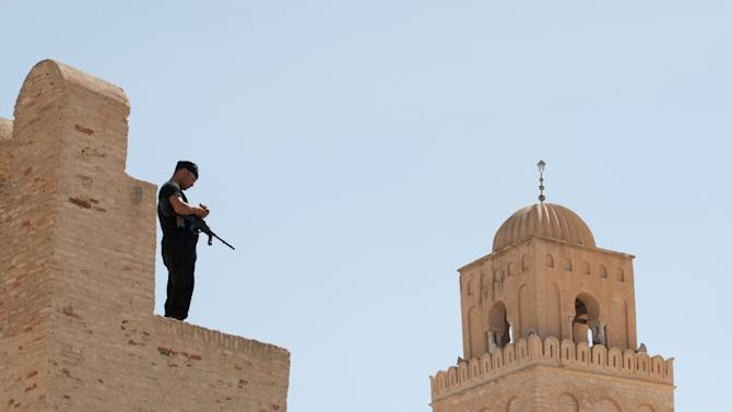 """A Tunisian security officer stands guard in the city of Kairouan where ultraconservative Islamic group, Ansar al-Shariah's, annual conference was supposed to be held, Sunday May 19, 2013. A massive Tunisian security presence has surrounded the country's main religious center of Kairouan and prevented hardline Muslims from holding their annual gathering. Some 11,000 police surrounded the city this weekend and patrolled inside to prevent the conference from taking place because """"of the threat it represented to security and public order."""" (AP Photo/ Amine Landoulsi)"""