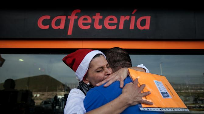 "Gas station worker, Maria Gonzalez Jimenez, hugs a colleague after winning the second prize of the Christmas lottery ""El Gordo"" (""The Fat One"") in Santa Cruz de Tenerife in the Canary Islands, Spain, Sunday Dec. 22, 2013. Millions of Spaniards are glued to televisions as the country's cherished Christmas lottery, the world's richest, distributes a bounty of 2.5 billion euros ($3.4 billion) in prize money to winning ticket owners. The draw is so popular that most of Spain's 46 million inhabitants traditionally watch some part of it live in the hope that the school children singing out winning numbers will call out their ticket. The top prize, known as ""El Gordo"" (The Fat One), gives lucky winners 400,000 euros per ticket Sunday, while the second-best number nets 125,000 euros. (AP Photo/Andres Gutierrez)"
