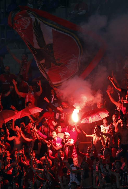 Fans of Egypt's Al Ahly fans light flares during their 2013 FIFA Club World Cup football match for fifth place against Mexico's Monterrey in Marrakech stadium