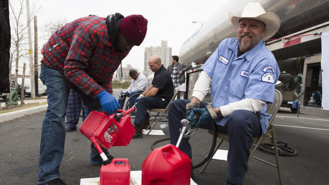 Brian Runestad, 44, a volunteer with Fuel Relief Fund, fills up gas cans for free in the Far Rockaways section of the Queens borough of New York, Saturday, Nov. 10, 2012.  Despite power returning to many neighborhoods in the metropolitan area, residents of the Far Rockaways continue to live without power and heat due to damage caused by Superstorm Sandy.(AP Photo/John Minchillo)