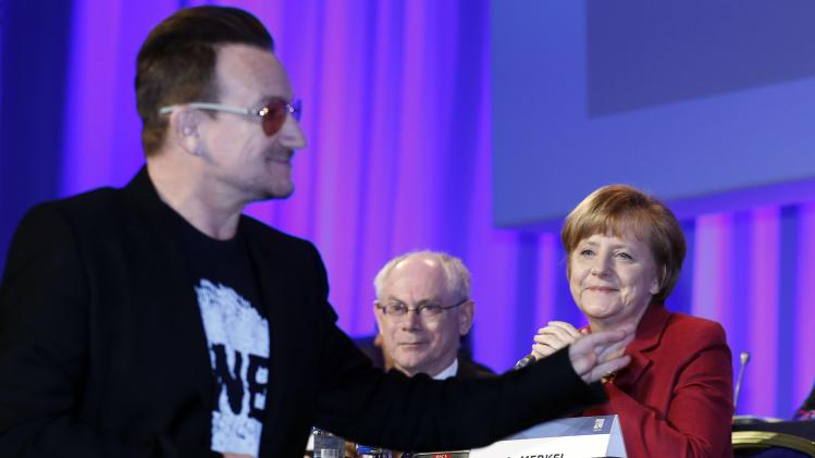 German Chancellor Merkel and European Council President Van Rompuy look on as singer Bono arrives at the European People's Party (EPP) Elections Congress in Dublin