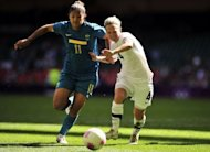Brazil's striker Cristiane (L) clashes with New Zealand's defender Katie Hoyle during their London 2012 Olympic Games women's football match at the Millennium Stadium in Cardiff, Wales. Brazil won 1-0