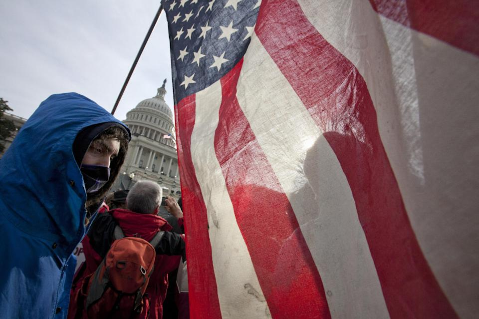 As Congress returns from its winter recess, protesters aligned with the Occupy Wall Street movement demonstrate on Capitol Hill in Washington, Tuesday, Jan. 17, 2012, to decry the influence of corporate money in politics.  (AP Photo/J. Scott Applewhite)
