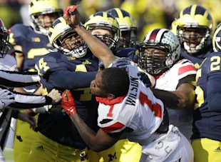 OSU's Dontre Wilson (1) throws a punch as the two teams scuffle Saturday. (AP)