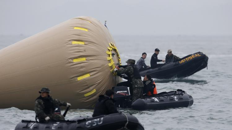 "Members from the South Korean Navy's SSU work on a buoy to mark the capsized passenger ship ""Sewol"" as they take part in a rescue operation at the sea off Jindo"
