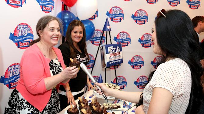 Lisa Hess-Marks, head baker at Crumbs bakery, left, and Erica Tucker, owner of Sweet E's, are interviewed during the kick-off of the Nestle Crunch 75th Birthday Showdown at Sweet E's on Wednesday, March 27, 2013 in Los Angeles. (Photo by Casey Rodgers/Invision for Nestle Crunch/AP Images)