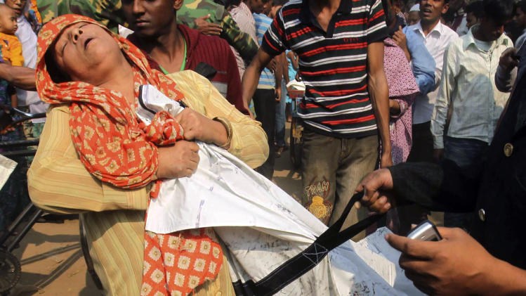 A Bangladeshi woman cries as she claims the body of her relative killed in a fire at a garment factory outside Dhaka, Bangladesh, Sunday Nov. 25, 2012. At least 112 people were killed in a late Saturday night fire that raced through the multi-story garment factory just outside of Bangladesh's capital, an official said Sunday.(AP Photo/ Jibon Amir)