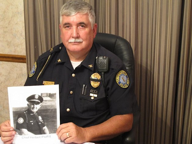 Tompkinsville Police Chief Dale Ford holds a photo of slain retired lawman Herbert Proffitt on Wednesday, Sept. 5, 2012, in Tompkinsville, Ky. Ford worked as a young officer years ago under the command of Proffitt, who was fatally shot outside his home late last month. (AP Photo/Bruce Schreiner)