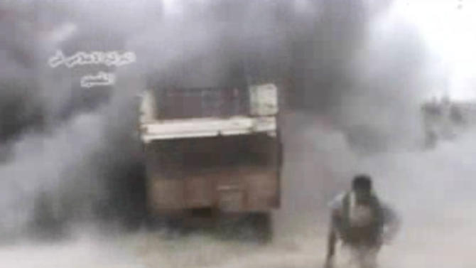AP10ThingsToSee - In this image from amateur video obtained by a group called Ugarit News, a rebel runs from an explosion, Sunday, May 19, 2013 in Qusair, Syria. An intense battle drove rebels from large parts of Qusair, part of a withering government offensive aimed at securing a strategic land corridor from Damascus to the Mediterranean coast. (AP Photo)