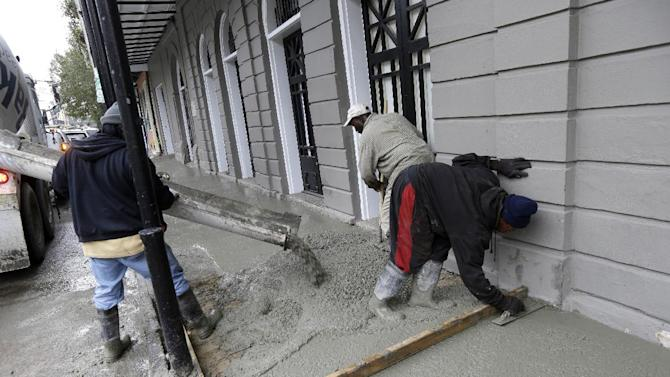 "This Jan. 15, 2013 photo shows workers pouring a new sidewalk on Royal Street in the French Quarter section of in New Orleans. With the Super Bowl in New Orleans Feb. 3 and Mardi Gras falling just nine days later, the city is gearing up for a massive celebration and influx of tourists that locals are calling ""Super Gras."" (AP Photo/Gerald Herbert)"