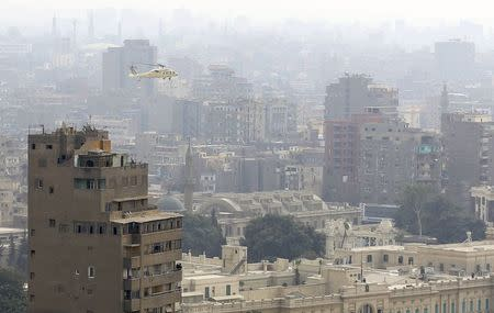 A reconnaissance military helicopter flies over Cairo