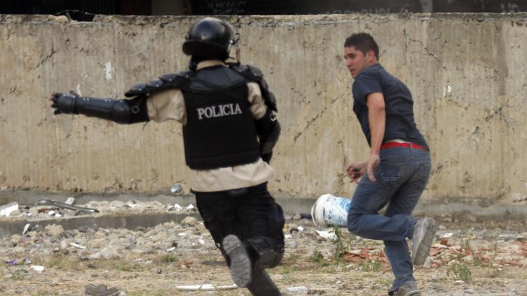 A national police chases after an anti-government protester at Altamira square in Caracas