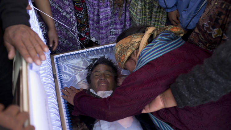 In this Oct. 5, 2012 photo, relatives mourn over the body of slain protester Francisco Ordonez during a funeral service in Totonicapan, Guatemala.  Experts said the arrest of soldiers in connection with the Oct. 4 killing of Indians protesting high electricity prices mark a dramatic shift in a country once known for its reluctance to punish its military. (AP Photo/Moises Castillo)
