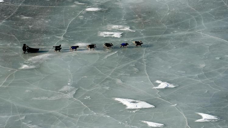 An Iditarod musher crosses a frozen pond between the Shaktoolik and Koyuk checkpoints during the 2014 Iditarod Trail Sled Dog Race on Sunday, March 9, 2014. (AP Photo/The Anchorage Daily News, Bob Hallinen)