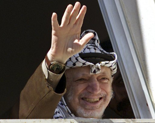 File photo of then Palestinian President Yasser Arafat waving to supporters from his window in the West Bank city of Ramallah