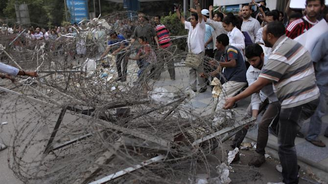 Protesters remove Egyptian security barbed wire blocking the road leading to Peoples' Assembly during a rally demanding the release of fellow activists, detained during the army operation that dispersed a protest in front of the Ministry of Defense, in Cairo, Egypt Sunday, May 6, 2012. (AP Photo/Nasser Nasser)
