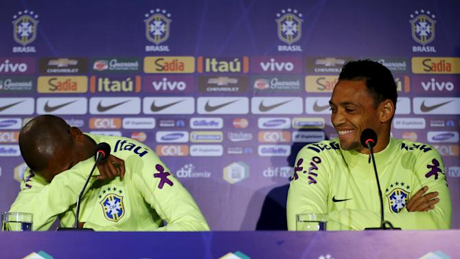 Brazil's players Ricardo Oliveira (R) and Fernandinho react after a question during a news conference before a team training session in Santiago