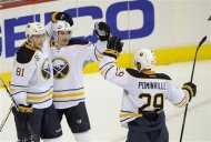 Buffalo Sabres center Jochen Hecht (55), of Germany, celebrates his goal with teammates Brayden McNabb (81) and Jason Pominville (29) during the second period of an NHL hockey game against the Washington Capitals, Friday, Dec. 30, 2011, in Washington. (AP Photo/Nick Wass)