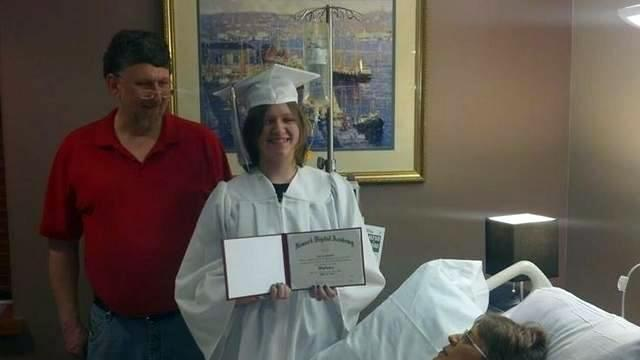 In this Monday, April 21, 2014 photo courtesy of Evie Shumaker, 17-year-old Evie Shumaker, of Newport, Ohio, displays her diploma after a special graduation ceremony in her mother's room at Licking Memorial Hospital in Newark, Ohio. Evie's mother, Melissa Shumaker has late-stage, inoperable pancreatic cancer, and Evie's teachers decided to award her a diploma early so her mother could see her graduate. (AP Photo/Courtesy Evie Shumaker)