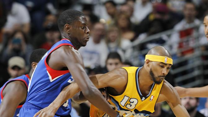 Denver Nuggets forward Corey Brewer, right, picks up a loose ball as Philadelphia 76ers guard Jrue Holiday covers in the first quarter of an NBA basketball game in Denver, Thursday, March 21, 2013. (AP Photo/David Zalubowski)