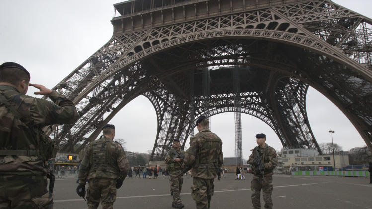A French soldier saluts as he patrols with his fellows infront of the Eiffel tower, Sunday, Jan. 13, 2013. France has ordered tightened security in public buildings and transport following action against radical Islamists both in Mali and Somalia, French President Francois Hollande said yesterday. (AP Photo/Michel Euler)