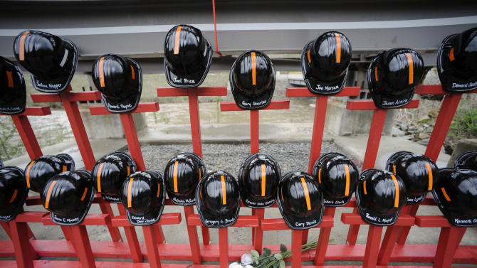 Mine helmets and painted crosses sit at the entrance to Massey Energy's Upper Big Branch coal mine Tuesday, April 5, 2011 in Montcoal, W.Va. The memorial represents the 29 coal miners who were killed in an explosion at the mine one year ago today. (AP Photo/Jeff Gentner)