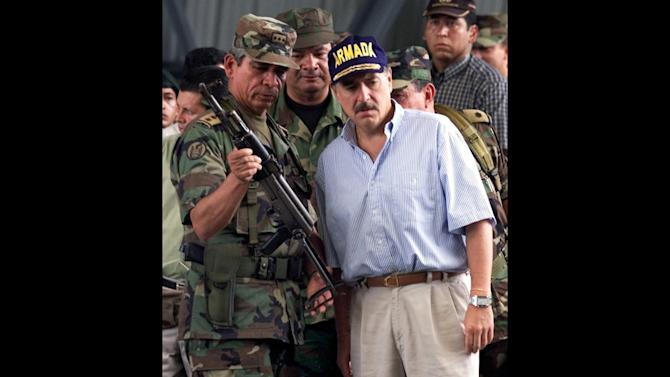 FILE - In this May 1, 2001 file photo, Gen. Jorge Enrique Mora, left, holds a weapon used by suspected paramilitary fighters in Buenaventura, about 215 miles southwest of Bogota, Colombia. Mora spent a professional lifetime battling Colombia's rebels. On Monday, Oct. 15, 2012 he sits down with them to talk peace, and the former armed forces chief may be the key to whether the negotiations that open in the Norwegian capital of Oslo succeed or fail. Former Colombian President Andres Patrana is pictured at right. (AP Photo/Scott Dalton, File)