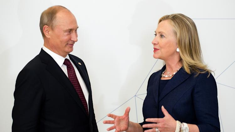 U.S. Secretary of State Hillary Rodham Clinton, right, talks with Russian President Vladimir Putin during the arrival ceremony for the Asia-Pacific Economic Cooperation (APEC) Summit in Vladivostok, Russia, Saturday, Sept. 8, 2012. (AP Photo/Jim Watson, Pool)