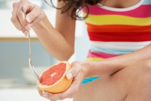 Woman eating grapefruit with a spoon