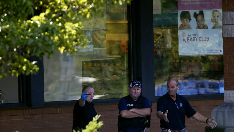 Officials investigate the scene of a shooting at a Pathmark grocery store in Old Bridge, N.J., Friday, Aug. 31, 2012.  Officials say a supermarket employee killed two people at the store early Friday and then fatally shot himself. Authorities say he opened fire on employees he saw when he walked into the Pathmark store. The store's front windows were shattered by gunfire.  The motive is being investigated. (AP Photo/Julio Cortez)