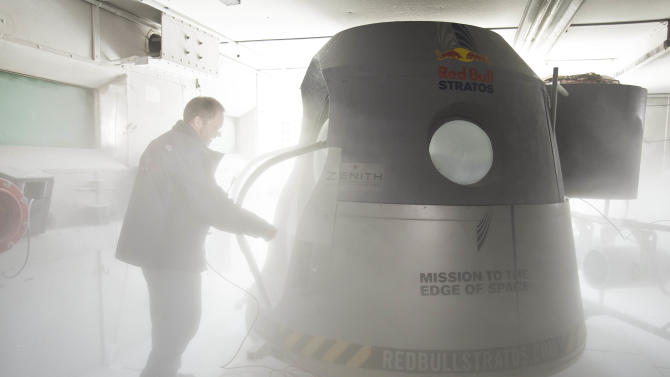 In this Sept. 24, 2012 photo, a crew member adjusts the space capsule of the Red Bull Stratos mission in the pressure chamber at Brooks Air Force Base in San Antonio, Texas. Skydiver Felix Baumgartner Baumgartner will attempt to go supersonic when he jumps from the capsule at a record altitude of 23 miles over New Mexico. On Tuesday, Sept. 25, 2012 project managers announced the jump is scheduled for Oct. 8, 2012. (AP Photo/Red Bull, Garth Milan)