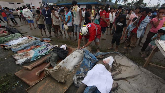 A rescuer covers bodies recovered from flashflood in New Bataan, Compostela Valley province, southern Philippines Wednesday, Dec. 5, 2012. The death toll from Typhoon Bhopa climbed over 280 Wednesday, while scores of others remain missing in the worst-hit areas of the southern Philippines. (AP Photo/Karlos Manlupig)