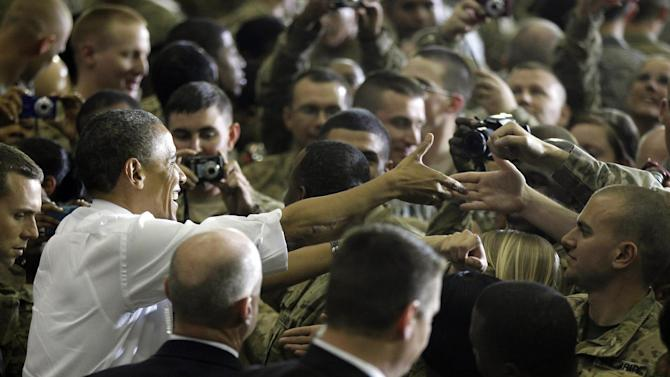 "FILE -In this May 2, 2012 file photo, President Barack Obama greets troops at Bagram Air Field, Afghanistan. As slogans go, President Barack Obama's promise of the ""light of a new day"" in Afghanistan isn't as catchy as the ""Mission Accomplished"" banner that hung across the USS Abraham Lincoln the day President George W. Bush announced the end of major combat operations in Iraq. (AP Photo/Charles Dharapak, File)"