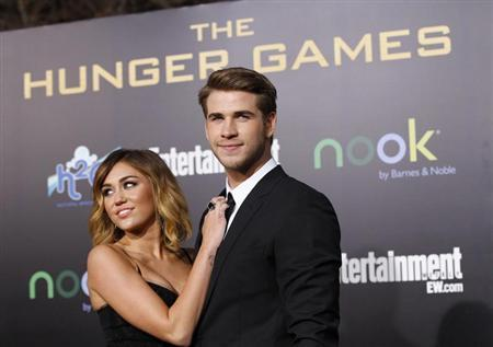 "Cast member Hemsworth poses with actress Cyrus at the premiere of ""The Hunger Games"" at Nokia theatre in Los Angeles"