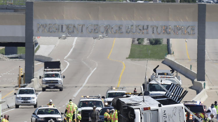 A charter bus rests on it's side after crashing on the President George Bush Turnpike Thursday, April 11, 2013, in Irving, Texas. The chartered bus overturned on the busy highway near Dallas killing at least two people and injuring several others, authorities said. (AP Photo/LM Otero)