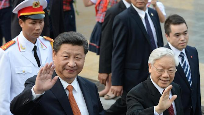 FILE - In this Nov. 5, 2015 file photo, Chinese President Xi Jinping, left, and Vietnamese Communist Party Secretary General Nguyen Phu Trong wave at well-wishers as they leave a welcome ceremony at the presidential palace for the headquarters of the Vietnamese Communist Party for official talks in Hanoi. Divided opinions within Vietnam's Communist Party on how to relate to giant neighbor and one-time ally China are among key factors in play at an eight-day congress to choose new leadership. During Xi's visit to Vietnam, Xi and Trong agree to limit their differences and maintain peace and stability. (Hoang Dinh Nam/Pool Photo via AP, File)