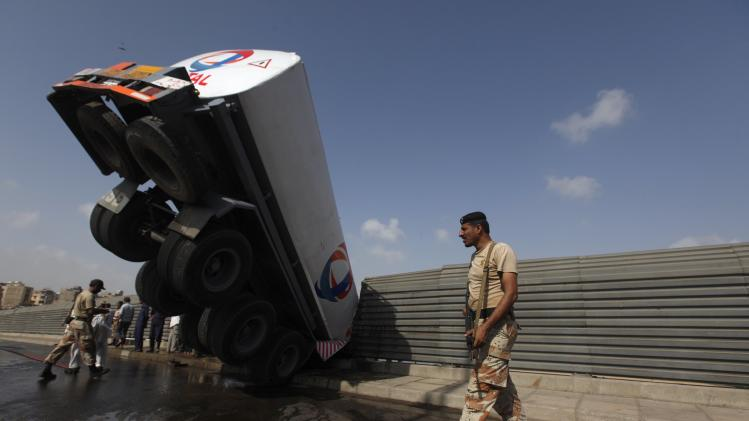 A Ranger soldier walks past an oil tanker, after it skidded and crashed on the side grill of a bridge, in Karachi