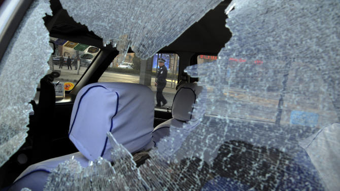 A Chinese police officer is framed by the glass window of a vehicle damaged by explosions outside the provincial headquarters of China's ruling Communist Party in Taiyuan in north China's Shanxi province Wednesday Nov. 6, 2013. The Shanxi provincial government and police said the blasts which killed one and injured eight struck at about 7:40 a.m. (2340 GMT Tuesday). (AP Photo) CHINA OUT