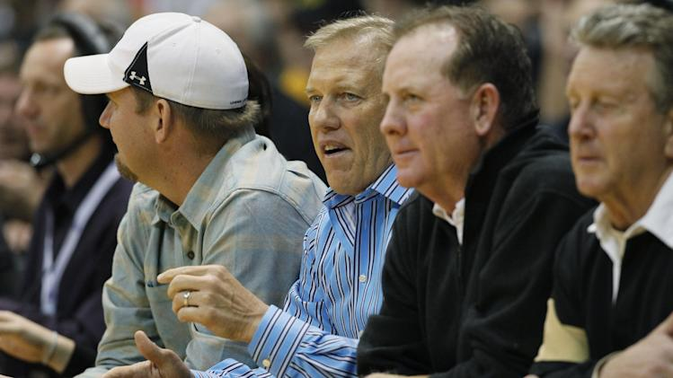 John Elway, center, executive vice president of football operations for the Denver Broncos, takes a courtside seat to watch Colorado host Arizona in the first half of an NCAA college basketball game in Boulder, Colo., on Thursday, Feb. 14, 2013. (AP Photo/David Zalubowski)