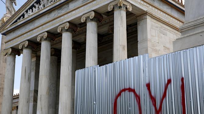 A NO graffiti is seen as Japanese tourists sit at the entrance of the Athens Academy