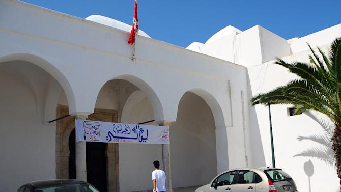 In this Thursday, July 26, 2012 photo a man enters an art gallery in La Marsa, Tunis. The Spring of the Arts exhibit in the wealthy Tunis suburb of La Marsa triggered June riots that left one dead and 100 injured. Many of the paintings questioned religion's role in society, including some clearly skewering Salafis. (AP Photo/Hassene Dridi)
