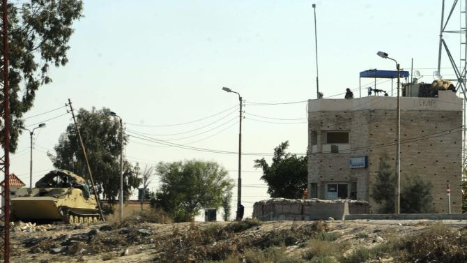 Egyptian soldiers stand guard at an army checkpoint in Arish, North Sinai