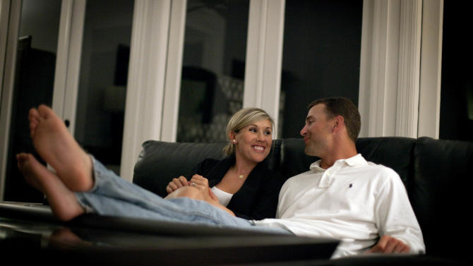 St. Louis Cardinals' Tyler Henley, right, sits with wife Blair in her parent's home Wednesday, March 30, 2011 in Palm Beach Gardens, Fla. Blair and Tyler Henley have been married for two and a half years yet they own no home, no furniture, and in a few days time will pack all their worldly possessions into two cars and make their ninth move as a newlywed couple.  (AP Photo/David Goldman)