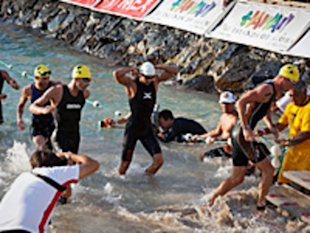 Luke Bell, leads triathletes exiting the water after the 2.4 mile swim portion of the Ford Ironman World Championship on Oct. 8, 2011 in Kailua-Kona, Hawaii.